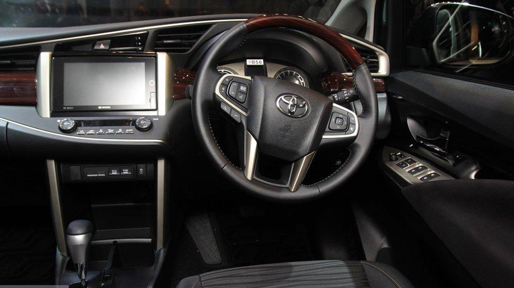 Toyota Innova 2016 sử dụng vô-lăng 4 chấu, bọc da và ốp vân gỗ sang trọng.