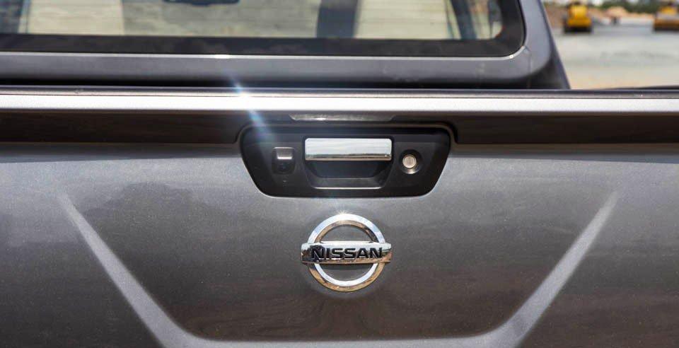 Đánh giá xe Nissan Navara 2015 có tay nắm thùng và logo mạ chrome.