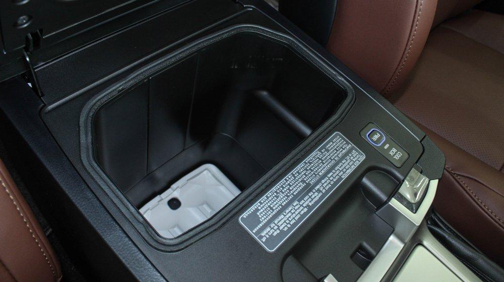 Đánh giá xe Land Cruiser 2016 có hộc đựng đồ dưới kệ tì tay phía hàng ghế trước.