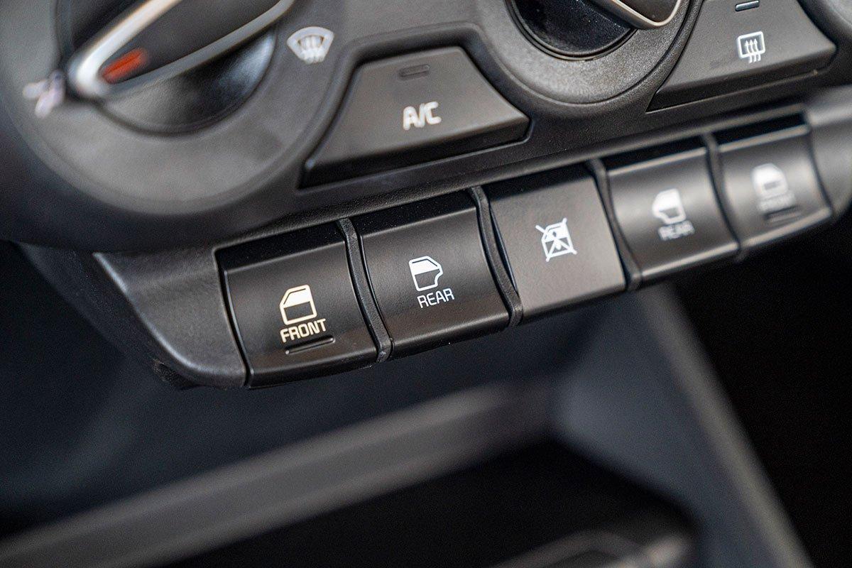 Đánh giá xe Kia Soluto 2019: Nút bấm nâng hạ kính được dịch chuyển vào bảng điều khiển trung tâm.