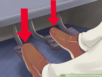 Nhấn cả chân côn và chân phanh.
