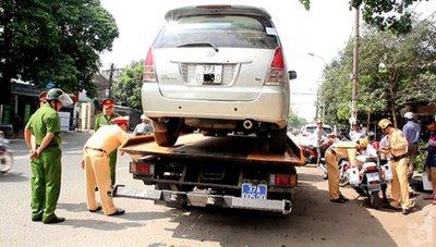 Lực lượng chức năng thu giữ xe ô tô vi phạm.